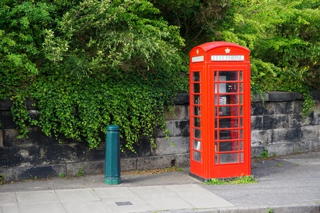 A vintage red British telephone booth stands by the roadside in Edinburgh, Scotland. Many of these iconic booths have been retired from service and are now being repurposed as sales kiosks and other uses. Banco de Imagens