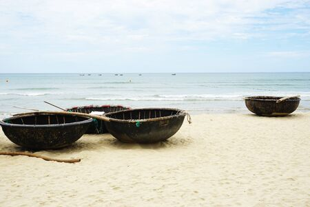 Fleet of traditional round woven bamboo coracle fishing boats on a sunny beach with blue sky overhead in rural Vietnam