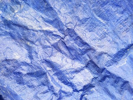 Crumbled blue plastic construction tarp abstract horizontal background texture
