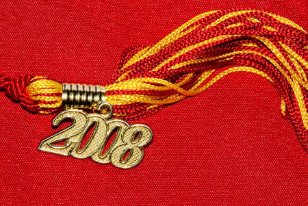 Tassel in red and gold with 2008 gold tag on red textured background.