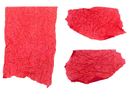 Three pieces of red tissue paper ripped, wrinkled and torn, isolated on a white background.
