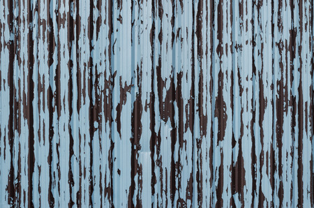 pale colours: Corrugated steel fence panel with flaking and peeling paint in the colours of brown and pale blue