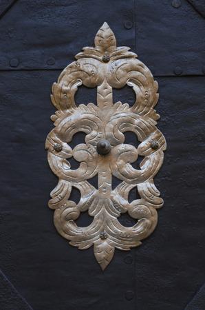 gold metal: Gold metal decoration on old black door
