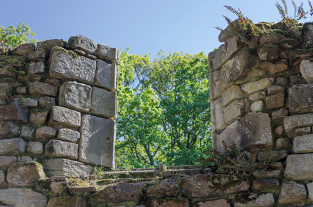 A partially collapsed window in an old stone monastery Stock Photo
