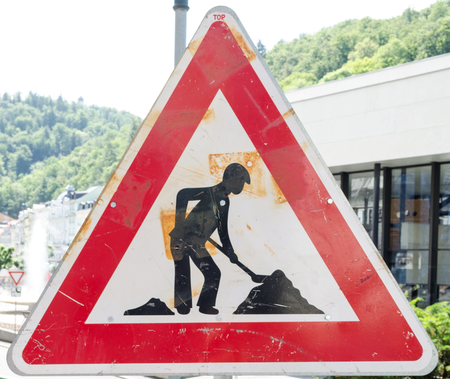 A rusty triangular sign warning of roadworks ahead with a modern city building in the background Stock Photo