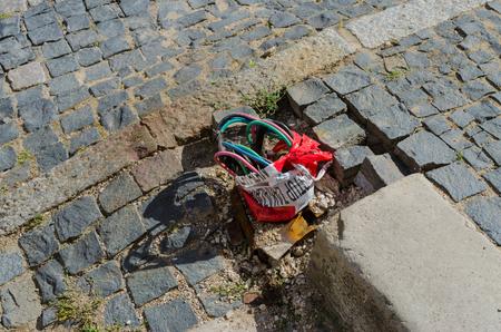 Câblage électrique exposé et non protégé sur un trottoir pavé ou une rue Banque d'images - 81639019