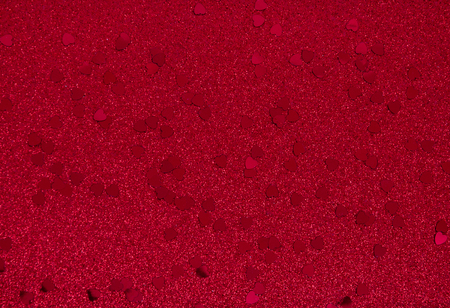 Tiny red metallic hearts on a red sparkly background with copy space Stock Photo
