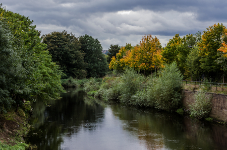 An urban landscape scene of an overgrown and neglected river in Northern England