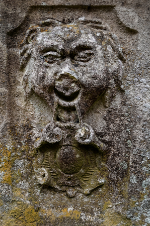 A face carved into a flat stone which has become weathered and worn