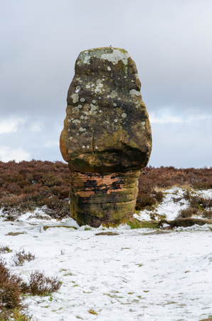Cork Stone on Stanton Moor is a cork shaped natural feature. The sandstone pillar has weathered to it's current shape through the centuries. The stone features steps carved, popular with climbers.  Stock Photo
