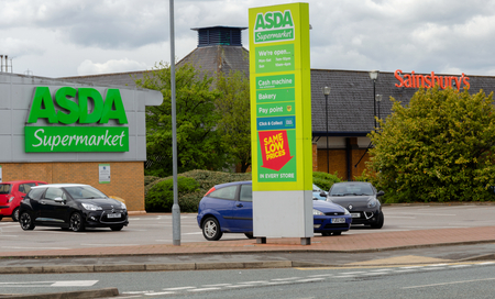 Flint, UK: May 1, 2018: Asda and Sainsbury who have announced a potential merger with no store closures are neighbours in the North Wales town of Flint.  Cars in the Asda car park with the Sainsbury s