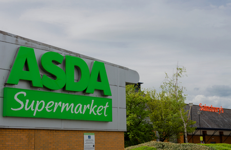 Flint, UK: May 1, 2018: Asda and Sainsbury who have announced a potential merger with no store closures are neighbours in the North Wales town of Flint.  Asdas logo on the frtont of their Flint store