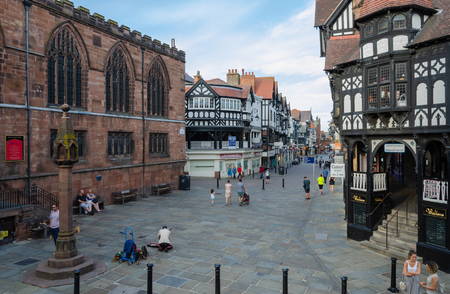 Chester, UK: Aug 6, 2018: General scene of the main shopping streets in Chester with many shoppers & tourists enjoying warm, sunny weather. Chester is a historic city, once populated by the Romans.