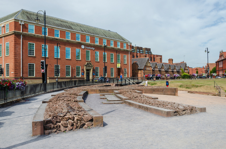 Chester, UK: Aug 6, 2018: A Travelodge hotel is directly opposite the remains of a Roman amphitheatre in the historic city of Chester.