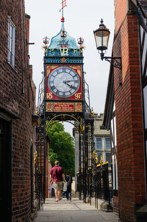Chester, UK: Aug 6, 2018: Tourists walk underneath the Eastgate clock whilst walking along the ancient Roman city walls of Chester.