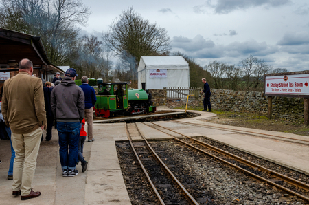 Shelley, UK: April 8, 2018: People watch from a platform whilst a narrow gauge steam train is turned round on a manually operated turntable. Kirklees Light Railway is a privately owned railway.