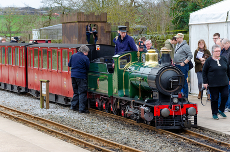 Shelley, UK: April 8, 2018: People watch as engineers attend to a narrow gauge steam train