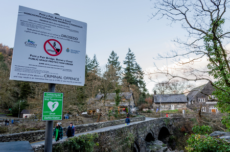 Betws y Coed, UK - Feb 2, 2019: The Pont-y-Pair bridge in Betws-y-Coed crosses the Afon Llugwy River. Signs warn of danger and fines for people who jump from the bridge into the river below.
