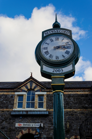 Betws y Coed, UK - Feb 2, 2019: A public time clock stands outside the main entrance to Betws y Coed railway Station in North Wales. Editorial