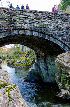 Betws y Coed, UK - Feb 2, 2019: The Pont-y-Pair bridge in Betws-y-Coed crosses the Afon Llugwy River. The bridge is a very popular photo location for tourists and travellers.