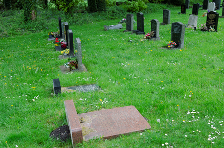Halkyn, UK - May 3, 2019: Grave headstones in the Parish church cemetery. Some have been laid flat as they were unstable and in danger of falling over.