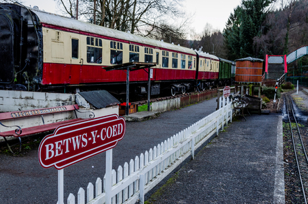 Betws-y-Coed, UK - Feb 2, 2019: The Conway Valley Railway Shop & Museum in Betws-y-Coed, North Wales. The platform for the narrow gauge railway with the catering carriage alongside. Zdjęcie Seryjne - 122328703