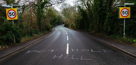 A road in Flintshire with the phrase pothole hill. Despite the road surface where the phrase is written on being in good condition.