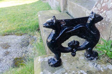 An ornamental cast iron boot scraper beside the entrance door of an old British church Reklamní fotografie