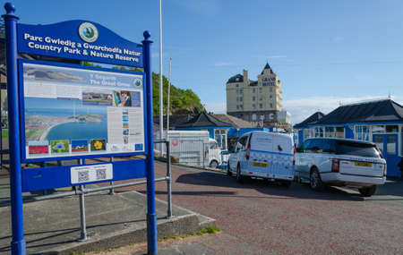 Llandudno, UK : May 6, 2019: A sign contains information about the Great Orme country park and nature reserve, adjacent to the pier at Llandudno. Local traders park their vehicles on the pavement. Editoriali