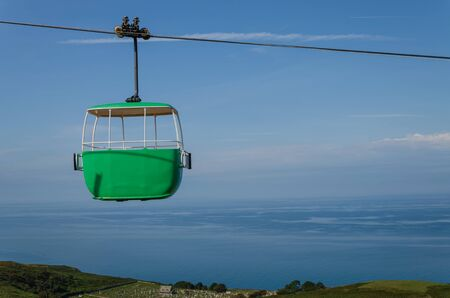 An empty cable car gondola soars through the sky above the Great Orme of Llandudno, North wales.