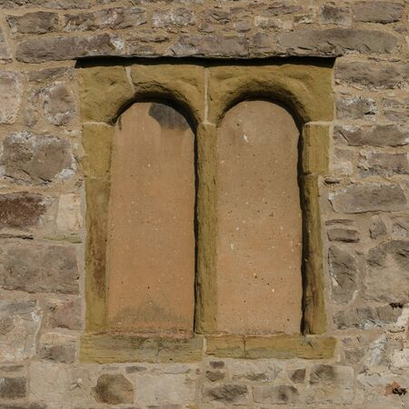 A pair of simple, arched church windows which have been blocked up.