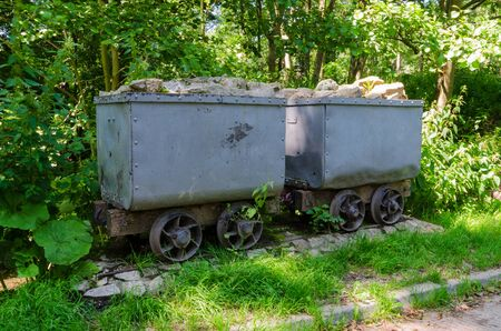 A pair of vintage mining wagons which run on rails. Wagons similar to these were used to transport stone, ore, minerals or coal in mines & quarries. They were drawn by horses, humans or locos.