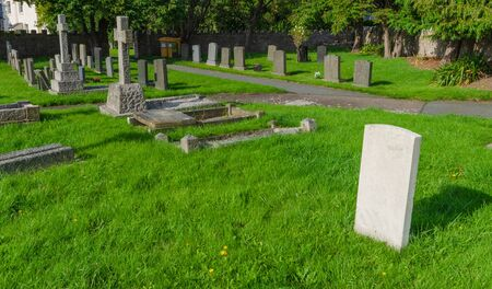 A typical British graveyard or cemetery with a variety of graves and a single headstone of Portland stone.
