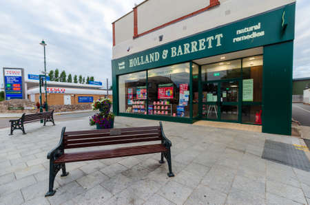 Prestatyn, UK: Jun 6, 2020: A general street scene in the town centre with the Holland & Barrett health food store in the foreground