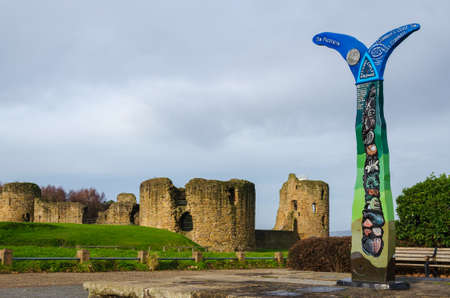 Flint; UK: Jan 28, 2021: A milepost beside Flint Castle gives directions and distances on the National Cycle Network. It was sponsored by the Royal Bank of Scotland as part of a Millenium Project.