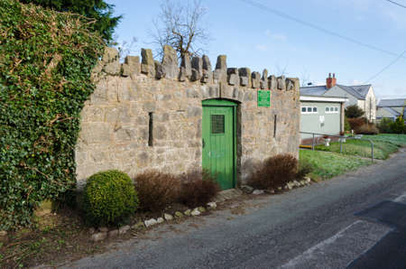 Caerwys, Flintshire; UK: Feb 11, 2021: The square, stone built shelter in Caerwys is a pinfold which would have been used in the past to house stray farm animals until they could be returned.