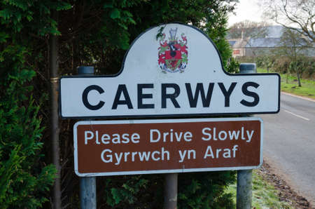 Caerwys, Flintshire; UK: Feb 11, 2021: A stone built name sign at the entrance to Caerwys incorporates the town's official coat of arms. A second sign asks motorists to please drive slowly