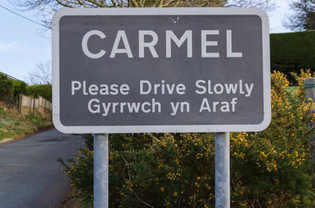 Carmel, Flintshire; UK: Feb 11, 2021: A place name sign at the entrance to the village of Carmel incorporates a bilingual Welsh and English message which asks motorists to please drive slowly