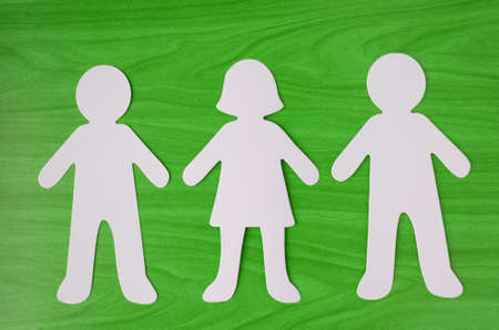 A paper cutout figure of a man, woman and man on a green wood grain background