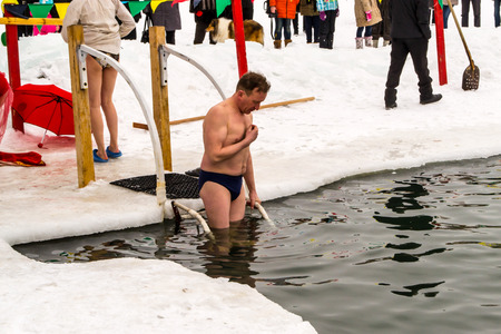 submerging: UFABASHKORTOSTAN RUSSIA 22nd February 2015 - A man prayers before submerging into ice cold waters for the Maslenitsa celebration in Russia Ufa