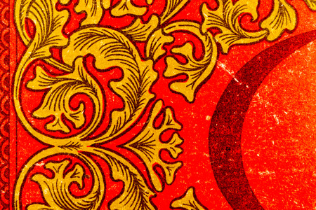 tatty: Red and gold patterns on paper with wear and in closeup