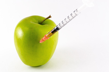 hypodermic: A hypodermic needle penetrates a fresh golden yellow apple in close up