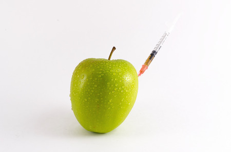 hypodermic syringes: A golden yellow apple pierced with a poisonous injection from a medical syringe needle