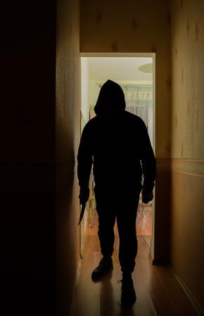 burglar man: A burglar man with a knife in darkness