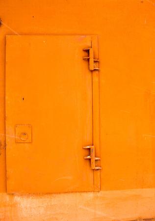 antique keyhole: A handpainted bright orange door with hinge