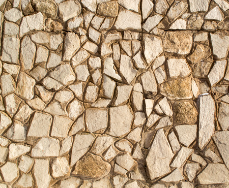 commercially: A commercially built brick wall with rocks and traditional cement