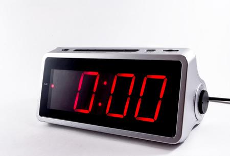 clocks: A retro looking silver digital alarm clock at midnight in red lights