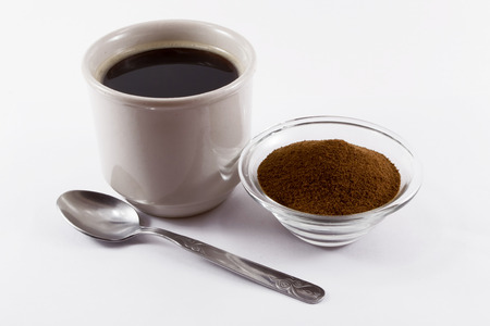 chicory coffee: A cup of hot chicory in a ceramic cup with a glass bowl of chicory powder and a silver tea spoon in the foreground on a white background