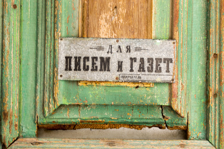 fading: UFABASHKORTOSAN - RUSSIA - 15th February 2015  An old russian door sign and antique fading wood An old russian door sign in cyrillic alphabet and antique fading wood