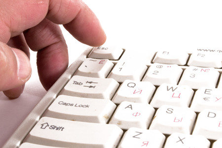 escape key: A male finger reaches to touch and press the escape key on a keyboard Stock Photo
